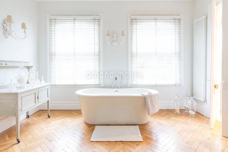 White, luxury home showcase bathroom with soaking tub and parquet hardwood floorの写真素材 [FYI02181996]