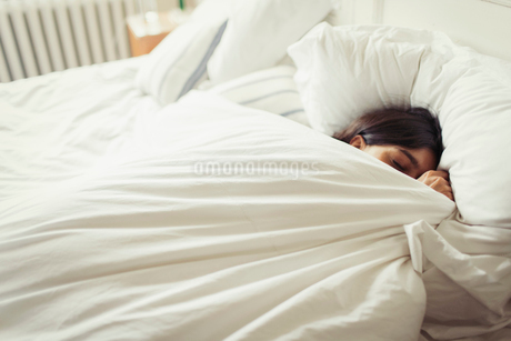 Tired young woman sleeping in bedの写真素材 [FYI02182004]
