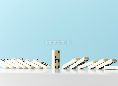 Dominos falling around standing domino against blue backgroundの写真素材 [FYI02182027]