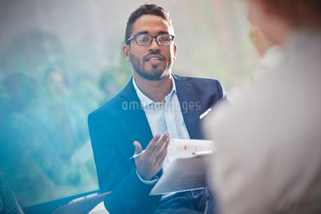 Man with clipboard talking in meetingの写真素材 [FYI02182056]
