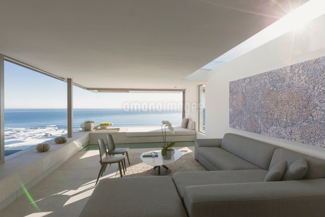Sunny modern, luxury home showcase interior living room with ocean viewの写真素材 [FYI02182097]