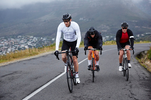 Dedicated male cyclists cycling on uphill roadの写真素材 [FYI02182108]