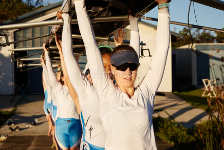 Confident, determined female rowing team lifting scull overhead on sunny dockの写真素材 [FYI02182122]