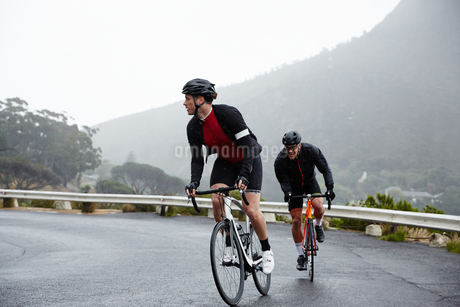 Dedicated male cyclists cycling on wet roadの写真素材 [FYI02182153]