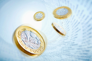 One pound coins surrounded by stock market dataの写真素材 [FYI02182168]