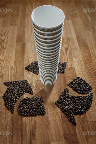 Coffee beans forming recycle symbol around stack of recyclable coffee cupsの写真素材 [FYI02182182]