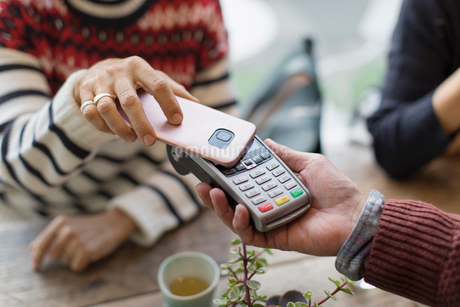 Woman with smart phone using contactless paymentの写真素材 [FYI02182235]