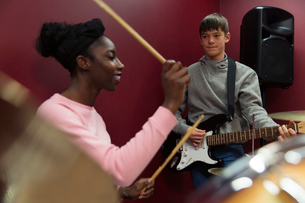 Teenage musicians recording music, playing guitar and drums in sound boothの写真素材 [FYI02182282]