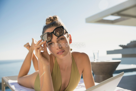 Portrait serious, confident woman in bathing suit and sunglasses sunbathing with digital tablet on sの写真素材 [FYI02182289]