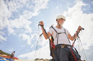 Mature male paraglider preparing equipmentの写真素材 [FYI02182302]