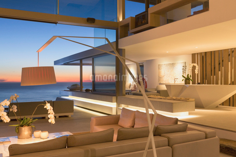 Illuminated, modern luxury home showcase interior living room with ocean view at duskの写真素材 [FYI02182312]