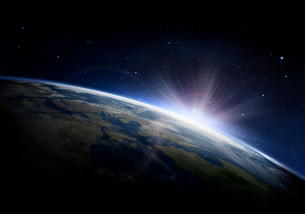 Sunlight ascending over Earth in outer spaceの写真素材 [FYI02182324]