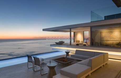 Illuminated modern, luxury home showcase exterior patio with sofa and lap pool with ocean view at duの写真素材 [FYI02182335]