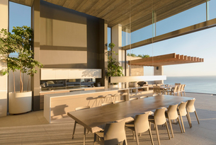 Sunny modern, luxury home showcase interior dining table with ocean viewの写真素材 [FYI02182340]