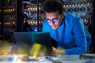 Focused male IT technician working at laptop in dark server roomの写真素材 [FYI02182342]