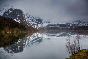 Reflection of snowy, rugged mountains in water, Storvatnet, Lofoten, Norwayの写真素材 [FYI02182354]