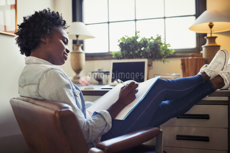 Businesswoman reviewing paperwork with feet up on deskの写真素材 [FYI02182357]