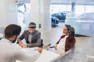 Car salesman explaining financial contract paperwork to pregnant couple customers in car dealershipの写真素材 [FYI02182373]