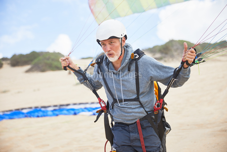 Focused mature male paraglider with equipment and parachute on beachの写真素材 [FYI02182405]