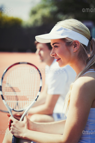 Smiling, confident female tennis player holding racket on sunny tennis courtの写真素材 [FYI02182415]