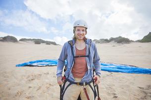 Portrait confident male paraglider on beachの写真素材 [FYI02182470]