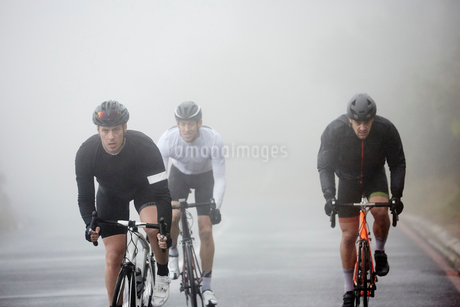 Dedicated male cyclists cycling on rainy roadの写真素材 [FYI02182521]