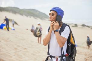 Male paraglider fastening helmet on beachの写真素材 [FYI02182522]