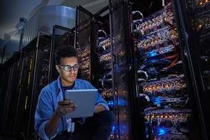 Focused male IT technician using digital tablet in dark server roomの写真素材 [FYI02182576]