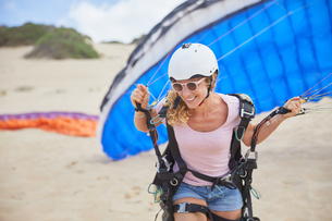 Smiling female paraglider with parachute on beachの写真素材 [FYI02182625]