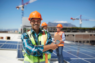 Portrait confident engineer installing solar panels on sunny rooftopの写真素材 [FYI02182648]
