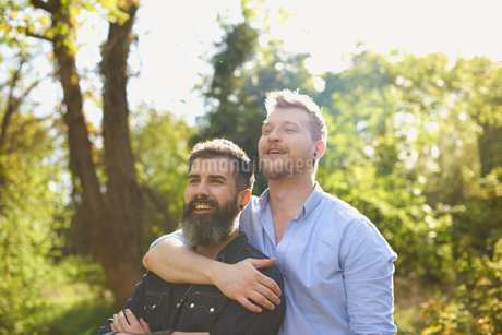 Affectionate male gay couple hugging in sunny parkの写真素材 [FYI02182689]