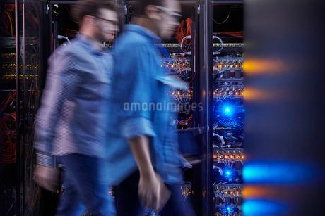Male IT technicians walking in dark server roomの写真素材 [FYI02182707]