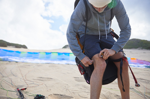 Male paraglider preparing equipment on beachの写真素材 [FYI02182727]