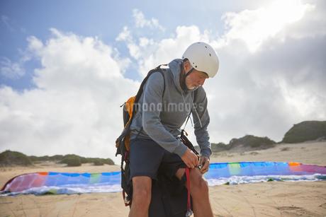 Male paraglider preparing on sunny beachの写真素材 [FYI02182734]