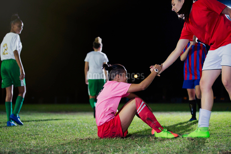Young female soccer player helping fallen teammate get up on field at nightの写真素材 [FYI02182841]