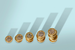 Ascending stacks of pound coins with bar graph growth shadowの写真素材 [FYI02182849]