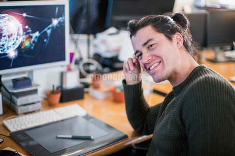 Portrait smiling, confident male graphic designer working at deskの写真素材 [FYI02183010]