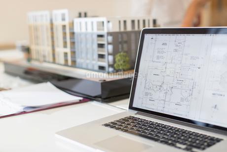 Digital blueprint on laptop next to modelの写真素材 [FYI02183120]