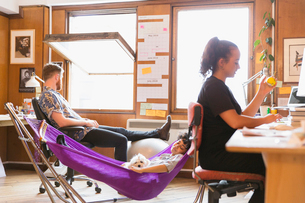 Creative female designer with dog napping in hammock in officeの写真素材 [FYI02183215]