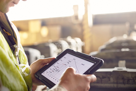 Close up steelworker reviewing digital graph on digital tablet in steel millの写真素材 [FYI02183221]