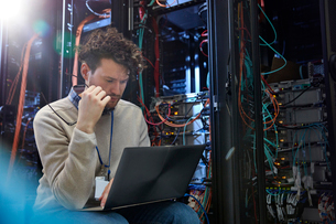 Focused male IT technician using laptop in server roomの写真素材 [FYI02183242]