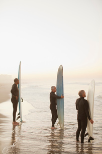 Older surfers holding boards on beachの写真素材 [FYI02183305]