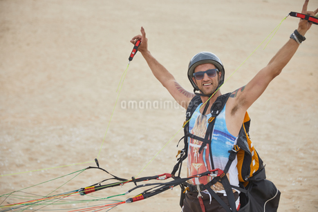 Portrait confident, carefree male paraglider strapped with equipment on beachの写真素材 [FYI02183339]