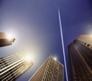Airplane and vapor trail in blue sky above highrise buildings, travel conceptの写真素材 [FYI02183367]