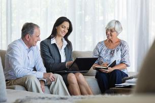 Financial advisor talking to couple on sofaの写真素材 [FYI02183444]