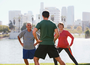 Older couple exercising with trainer in parkの写真素材 [FYI02183461]