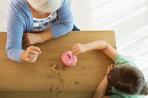 Older woman and granddaughter filling piggy bankの写真素材 [FYI02183499]