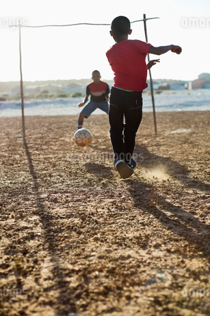 Boys playing soccer together in dirt fieldの写真素材 [FYI02183512]