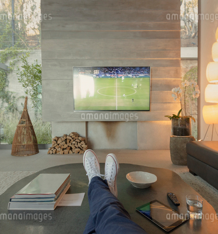 Personal perspective woman watching soccer on TV in living roomの写真素材 [FYI02183575]