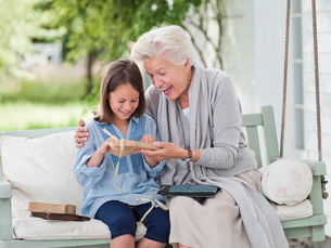 Woman giving granddaughter present in porch swingの写真素材 [FYI02183583]